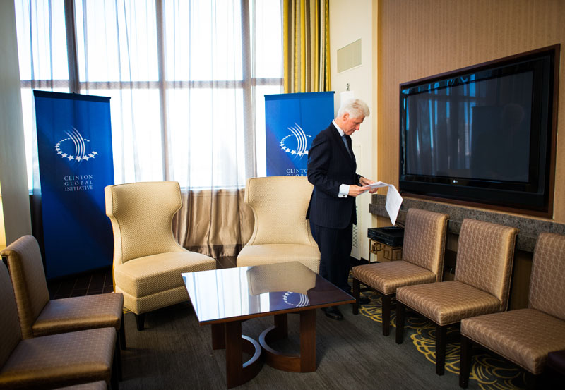 President Clinton checks briefing material in his hotel suite, which has been converted into a meeting room, before the arrival of a visiting head of state.