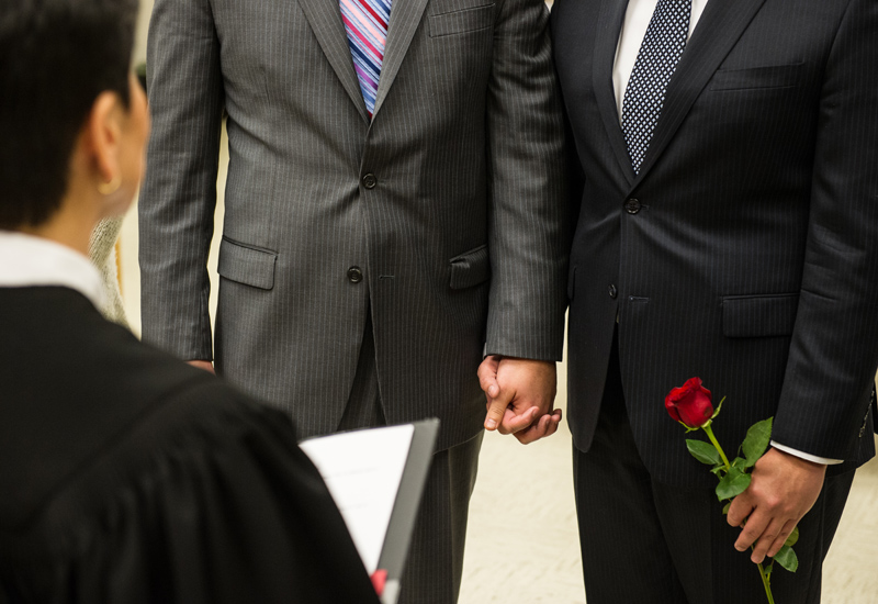 Brendan Taga and Jesse Page hold hands during their ceremony.
