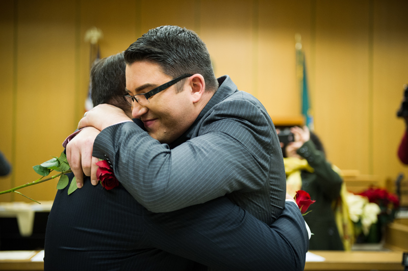 Jesse Page embraces his new spouse, Brendan Taga, after their wedding ceremony.