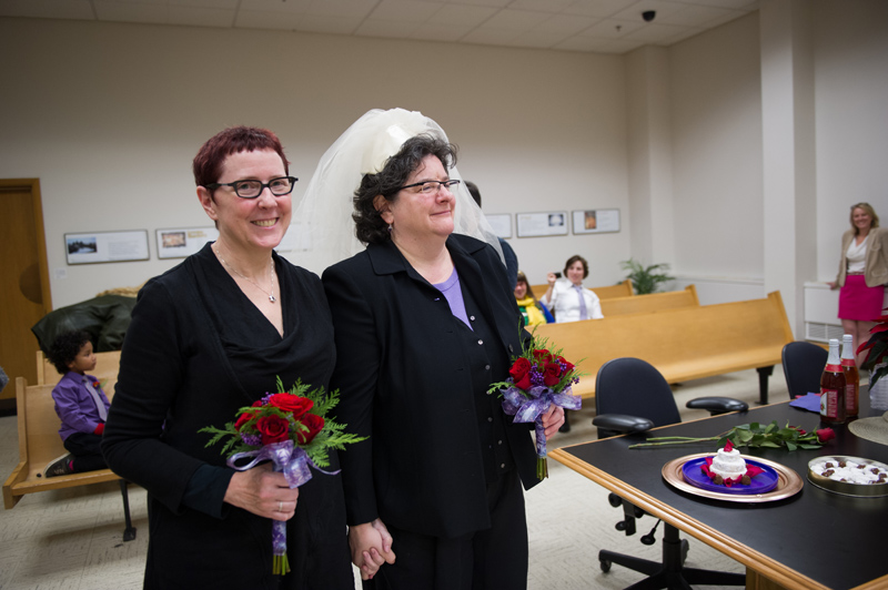 "Cynthia Wallace and Julie Fein walk ""down the aisle."" Julie is wearing a veil that their neighbor gave them that evening."