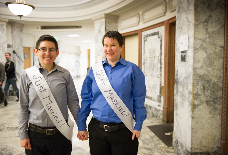 Tamara Neely and Caitlin Tinney with their hand-made wedding sashes, leave the courthouse.