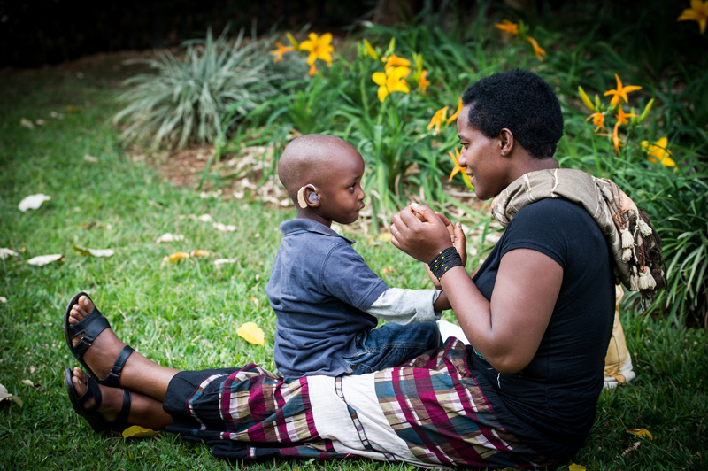 A young boy who was just fitted with a hearing aid at the Starkey Hearing Foundation event in Kigali, Rwanda listens to his mother speaking.