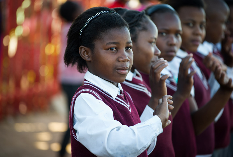 Young school girls perform a song for the Clinton Foundation delegation outside the clinic in South Africa.