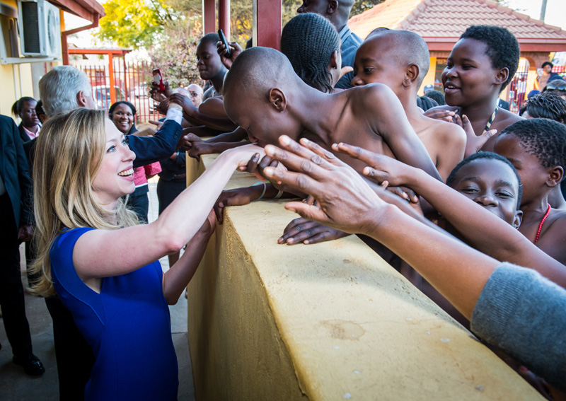 Chelsea Clinton is greeted by kids outside the Ramotse Clinic, a Clinton Health Access Initiative (CHAI) grantee, in South Africa.